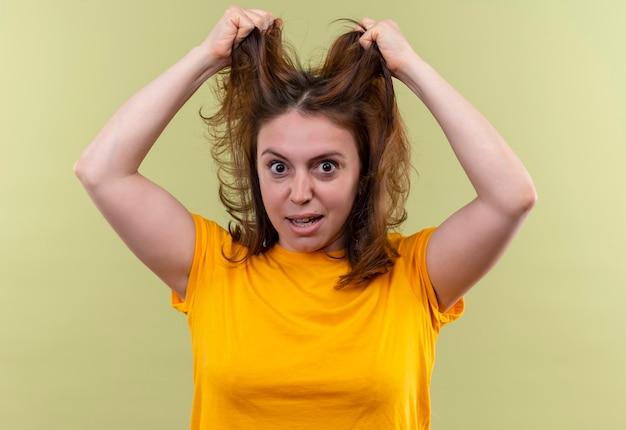 Impressionné jeune femme décontractée tenant ses cheveux sur un espace vert isolé