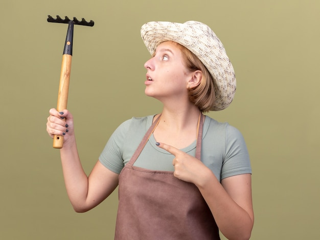 Impressionné jeune femme jardinier slave portant chapeau de jardinage tenant et pointant sur râteau isolé sur mur vert olive avec espace copie