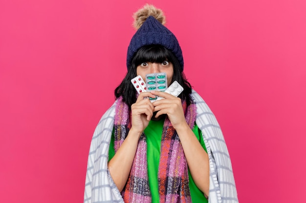 Impressionné jeune femme malade portant un chapeau d'hiver et une écharpe enveloppée dans un plaid tenant des paquets de pilules médicales devant la bouche à l'avant isolé sur un mur rose avec espace de copie