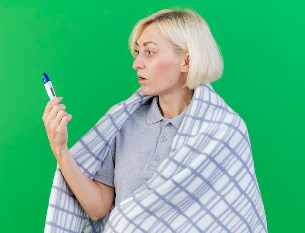 Impressionné jeune femme slave malade blonde enveloppée dans des cales à carreaux et regarde thermomètre isolé sur mur vert avec espace copie
