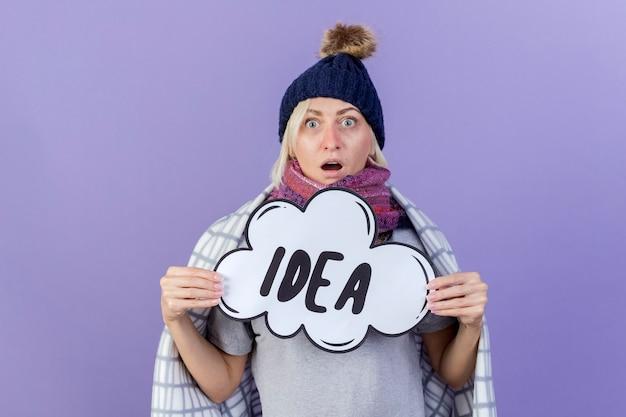 Impressionné jeune femme slave malade blonde portant un chapeau d'hiver et une écharpe enveloppée dans un plaid détient bulle idée isolée sur mur violet avec espace copie