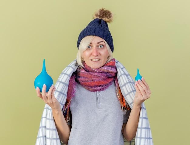 Impressionné jeune femme slave malade blonde portant un chapeau d'hiver et une écharpe enveloppée dans un plaid détient des lavements isolés sur un mur vert olive avec espace copie