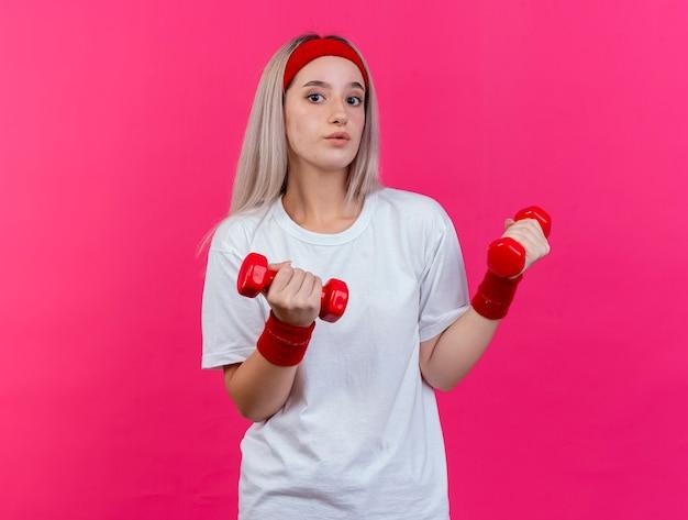 Impressionné jeune femme sportive avec des accolades portant un bandeau et des bracelets détient des haltères isolés sur un mur rose