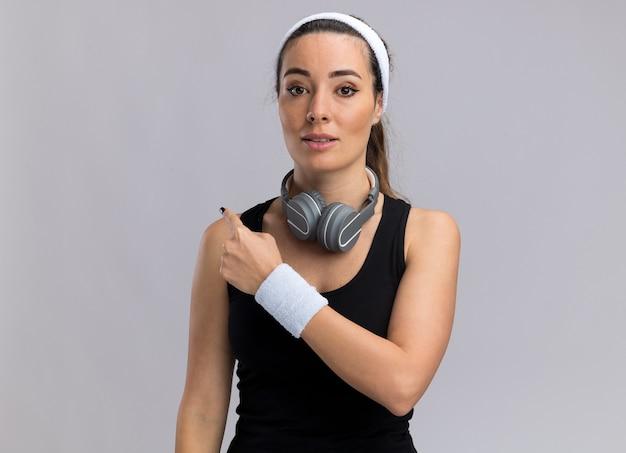 Impressionné jeune fille assez sportive portant un bandeau et des bracelets avec des écouteurs autour du cou pointant derrière