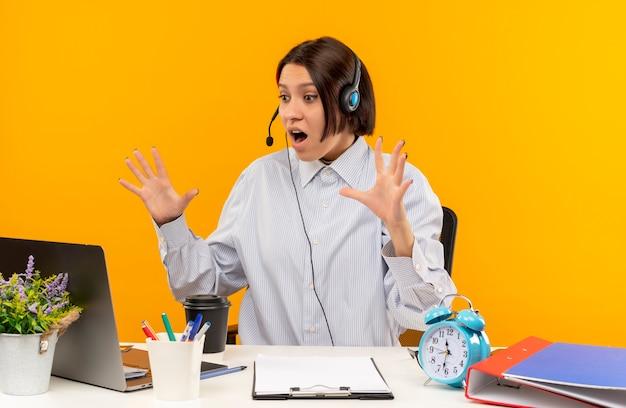 Impressionné jeune fille de centre d'appels portant un casque assis au bureau en regardant un ordinateur portable avec les mains surélevées isolé sur orange