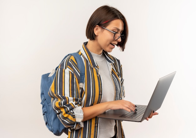 Impressionné jeune fille étudiante portant des lunettes et sac à dos à l'aide d'un ordinateur portable isolé sur blanc