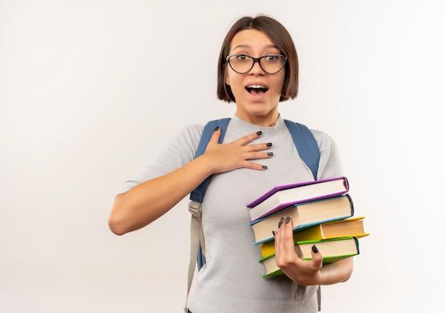 Impressionné jeune fille étudiante portant des lunettes et sac à dos tenant des livres mettant la main sur la poitrine isolé sur blanc