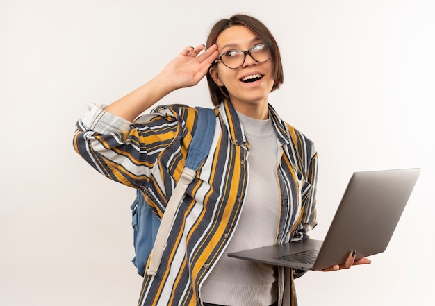 Impressionné jeune fille étudiante portant des lunettes et sac à dos tenant un ordinateur portable à côté de mettre la main sur le temple isolé sur blanc