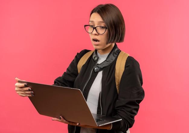Impressionné jeune fille étudiante portant des lunettes et sac à dos tenant et regardant un ordinateur portable isolé sur rose
