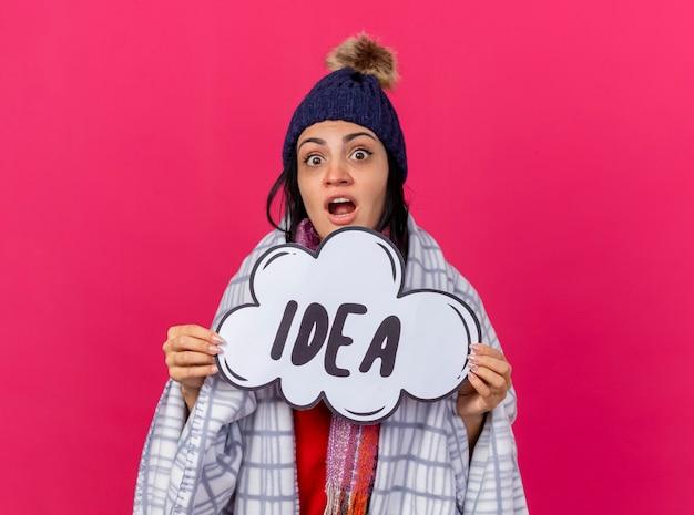 Impressionné jeune fille malade de race blanche portant un chapeau d'hiver et une écharpe enveloppée dans un plaid en regardant la caméra tenant la bulle d'idée isolée sur fond cramoisi avec espace de copie