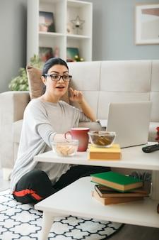 Impressionné jeune fille portant des lunettes utilisé un ordinateur portable assis sur le sol derrière une table basse dans le salon