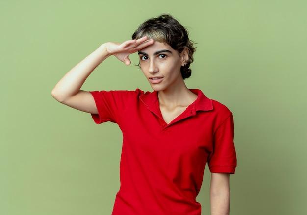 Impressionné jeune fille de race blanche avec coupe de cheveux de lutin mettant la main sur le front en regardant à distance isolé sur fond vert olive avec espace de copie