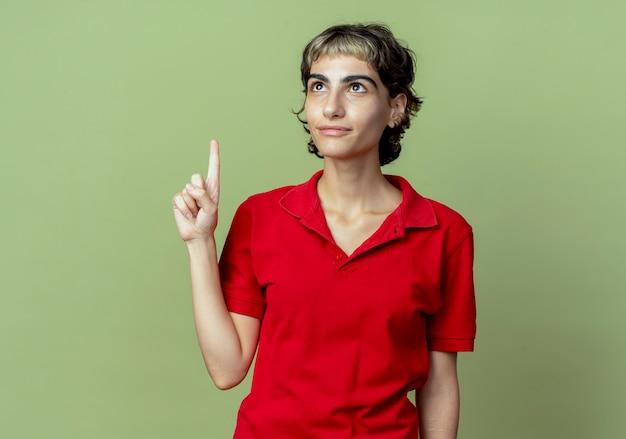 Impressionné jeune fille de race blanche avec coupe de cheveux de lutin à la recherche et pointant vers le haut isolé sur fond vert olive avec espace de copie