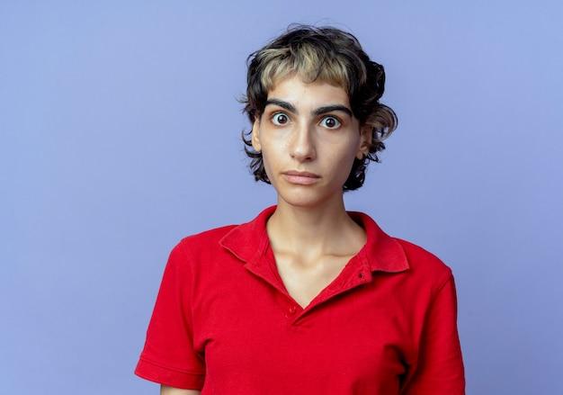 Impressionné jeune fille de race blanche avec coupe de cheveux de lutin regardant la caméra isolée sur fond violet avec espace de copie