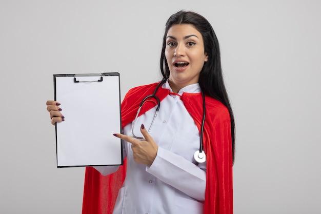 Impressionné jeune fille de super-héros de race blanche portant un stéthoscope montrant le presse-papiers en regardant la caméra isolée sur fond blanc avec copie espace