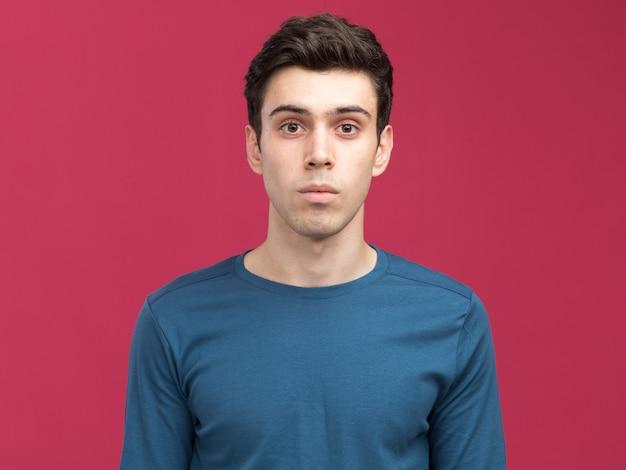 Impressionné jeune garçon caucasien brune regardant la caméra sur rose