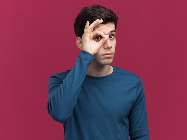 Impressionné jeune garçon caucasien brune regardant la caméra à travers les doigts sur rose
