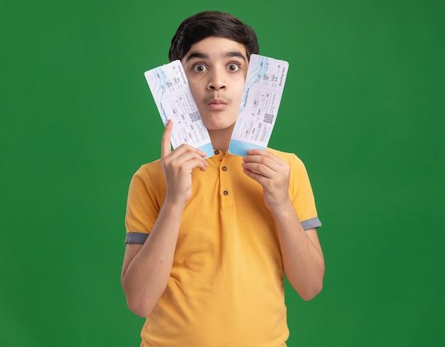 Impressionné jeune garçon caucasien tenant des billets d'avion touchant le visage avec eux
