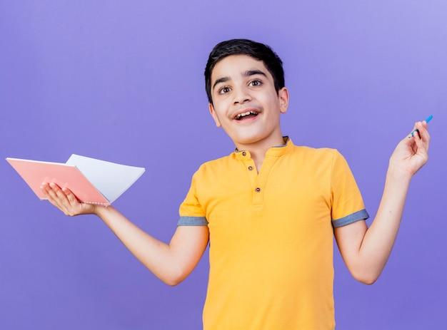 Impressionné jeune garçon caucasien tenant un bloc-notes et un crayon isolé sur un mur violet