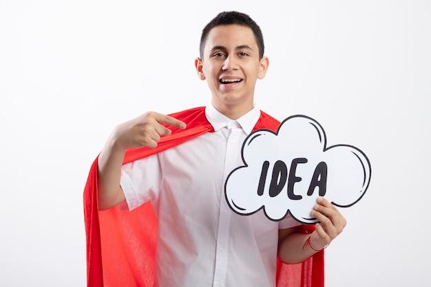 Impressionné jeune garçon de super-héros en cape rouge regardant la caméra tenant et pointant sur la bulle d'idée isolé sur fond blanc