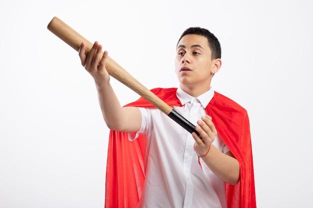Impressionné jeune garçon de super-héros en cape rouge tenant et regardant la batte de baseball isolé sur fond blanc