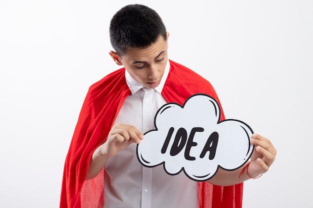 Impressionné jeune garçon de super-héros en cape rouge tenant et regardant la bulle d'idée isolée sur fond blanc
