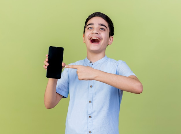 Impressionné jeune garçon tenant et pointant sur téléphone mobile à l'avant isolé sur mur vert olive