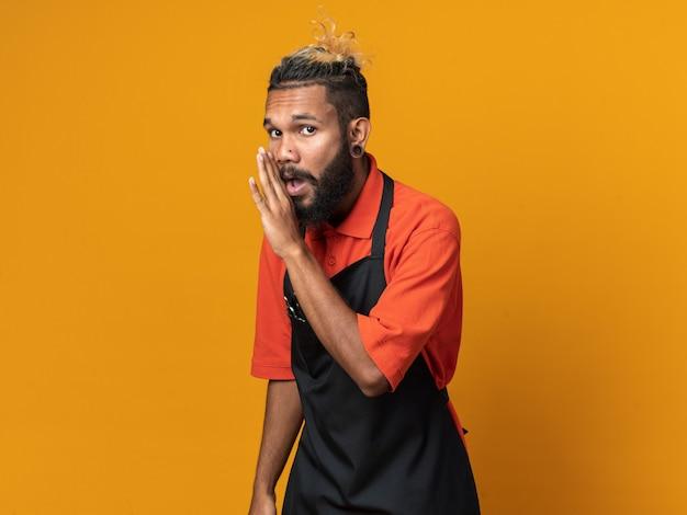 Impressionné jeune homme barbier en uniforme debout dans la vue de profil regardant le chuchotement avant isolé sur mur orange avec espace de copie
