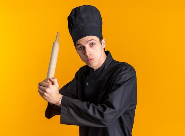 Impressionné jeune homme blond cuisinier en uniforme de chef et casquette debout en vue de profil tenant un rouleau à pâtisserie avec les deux mains