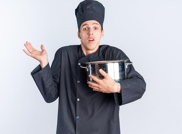Impressionné jeune homme blond cuisinier en uniforme de chef et casquette tenant un pot regardant la caméra montrant une main vide isolée sur un mur blanc