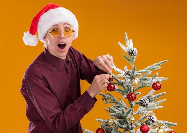 Impressionné jeune homme blond portant bonnet de noel et lunettes debout en vue de profil près de l'arbre de noël le décorant avec des boules de noël regardant la caméra isolée sur fond orange