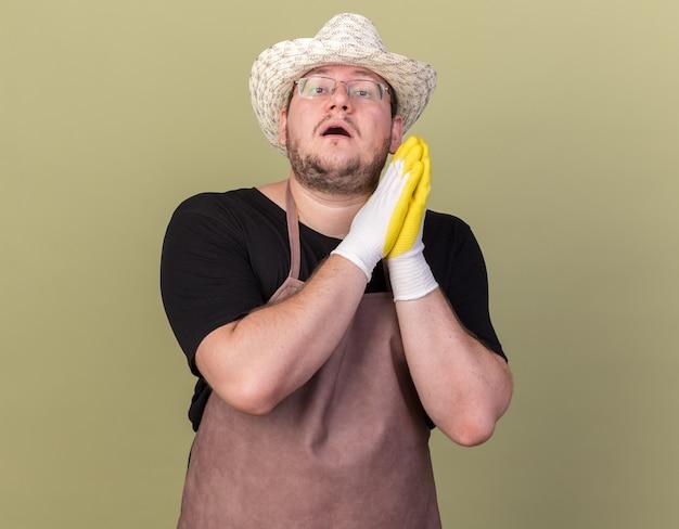 Impressionné jeune homme jardinier portant chapeau de jardinage et gants tenant par la main ensemble isolé sur mur vert olive
