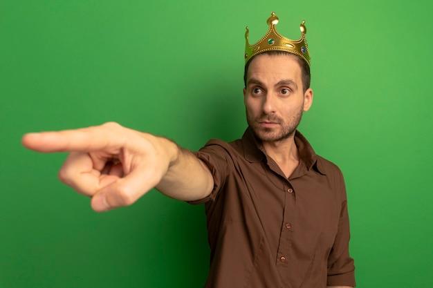 Impressionné jeune homme portant couronne à la recherche et pointant sur le côté isolé sur mur vert