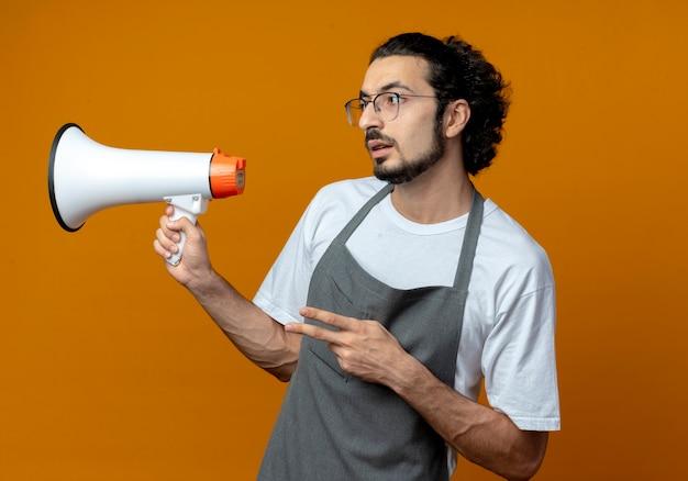 Impressionné jeune homme de race blanche coiffeur portant l'uniforme et des lunettes tenant le haut-parleur et faisant signe de paix et regardant côté isolé sur fond orange