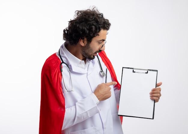 Impressionné jeune homme de race blanche à lunettes optiques portant l'uniforme de médecin avec manteau rouge et avec stéthoscope autour du cou regarde et pointe au presse-papiers tenant un crayon isolé sur un mur blanc