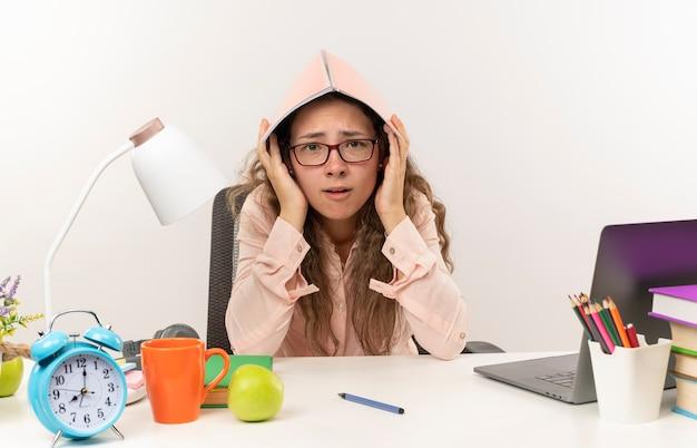 Impressionné jeune jolie écolière portant des lunettes assis au bureau avec des outils scolaires à faire ses devoirs en mettant le bloc-notes sur la tête isolé sur blanc