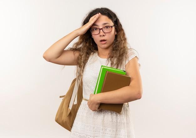 Impressionné jeune jolie écolière portant des lunettes et sac à dos tenant des livres mettant la main sur la tête isolé sur blanc