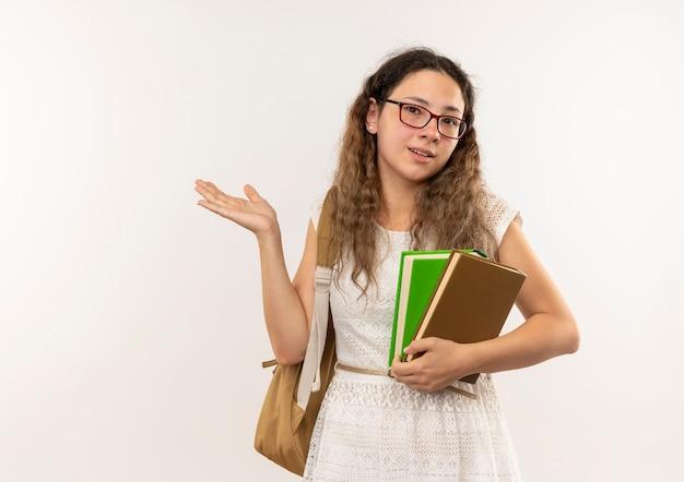 Impressionné jeune jolie écolière portant des lunettes et sac à dos tenant des livres montrant la main vide isolé sur blanc