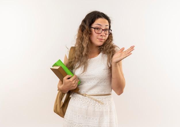 Impressionné jeune jolie écolière portant des lunettes et sac à dos tenant des livres montrant la main vide isolée sur