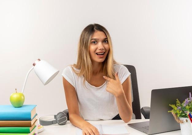 Impressionné jeune jolie étudiante assise au bureau avec des outils scolaires pointant sur elle-même isolé sur blanc