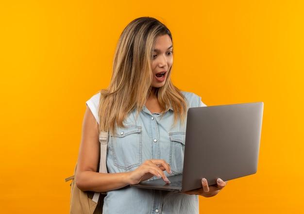 Impressionné jeune jolie étudiante portant un sac à dos à l'aide et en regardant un ordinateur portable isolé sur orange