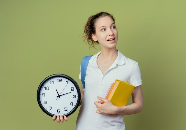 Impressionné jeune jolie étudiante portant un sac à dos à la recherche de côté tenant un livre et un bloc-notes avec horloge isolé sur fond vert avec espace de copie