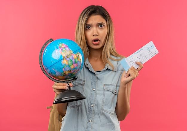 Impressionné jeune jolie étudiante portant sac à dos tenant billet d'avion et globe isolé sur rose