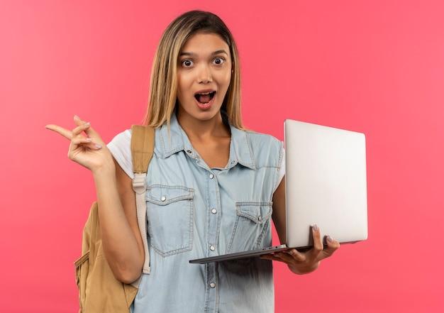 Impressionné jeune jolie étudiante portant un sac à dos tenant un ordinateur portable et pointant sur le côté isolé sur rose