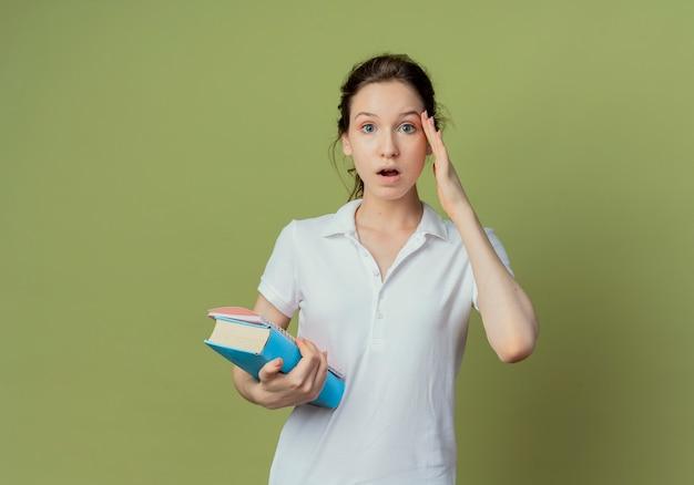 Impressionné jeune jolie étudiante tenant livre et bloc-notes mettant la main sur le visage isolé sur fond vert olive avec espace de copie