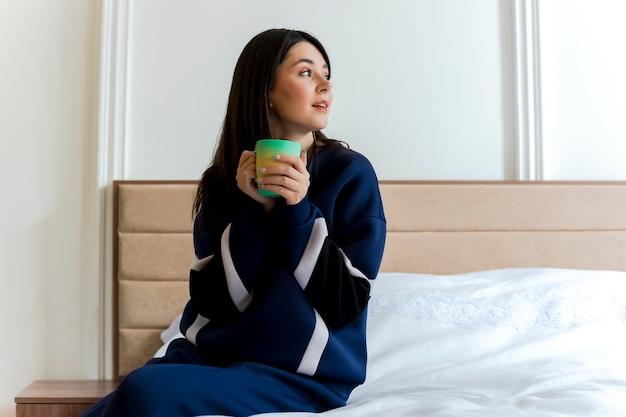 Impressionné jeune jolie fille caucasienne assise sur le lit dans la chambre à coucher tenant la tasse et regardant à côté