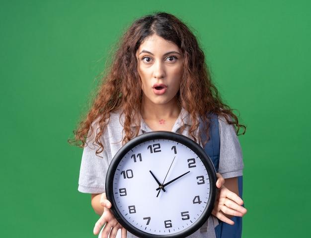 Impressionné jeune jolie fille caucasienne portant un sac à dos tenant une horloge