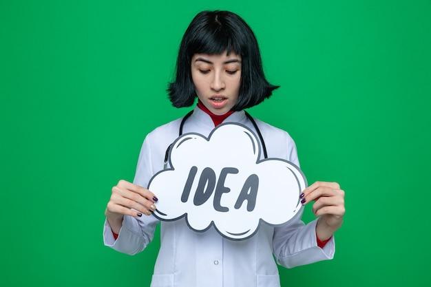 Impressionné jeune jolie fille caucasienne en uniforme de médecin avec stéthoscope tenant et regardant la bulle d'idée