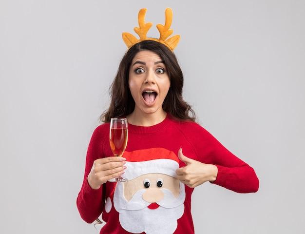 Impressionné jeune jolie fille portant bandeau de bois de renne et pull du père noël tenant un verre de champagne à la recherche de pouce vers le haut