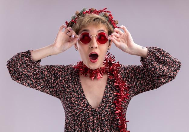 Impressionné jeune jolie fille portant couronne de tête de noël et guirlande de guirlandes autour du cou avec des lunettes à la recherche de lunettes de saisie latérale isolé sur fond blanc
